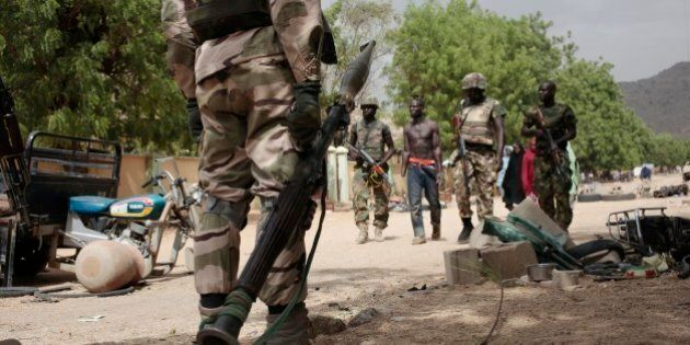 In this photo taken Wednesday, April 8, 2015, soldiers escort Hassan Usman, a forced laborer for Boko...