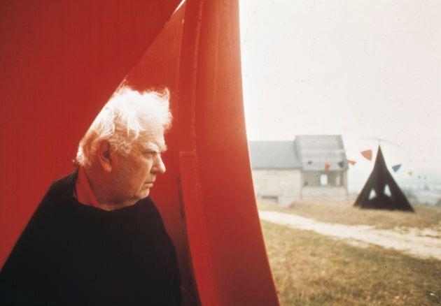 Alexander Calder pose à l'intérieur de l'une de ses oeuvres près de sa maison à Saché, en