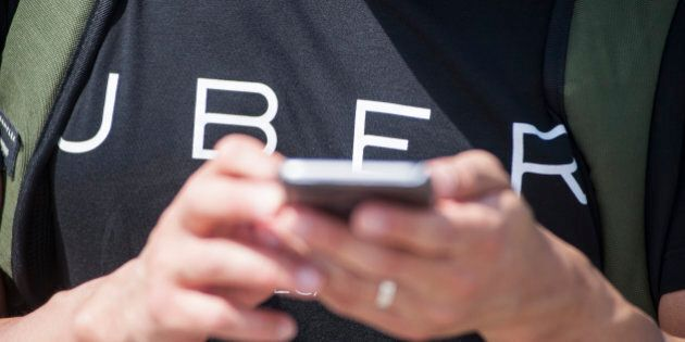 CANBERRA, AUSTRALIA - OCTOBER 30: Uber staff track the first regulated UberX ride in Australia on October...