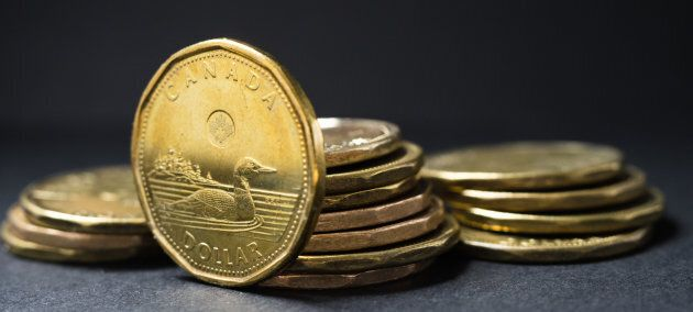 A Canadian dollar coin standing in front of coins