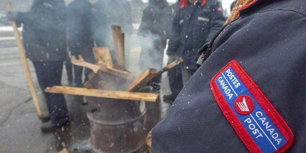Les travailleurs de Postes Canada sur la ligne de piquetage quelques heures avant l'adoption de la loi