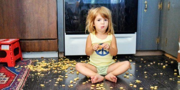 Toddler spills a snack all over the floor, but seems content to eat it