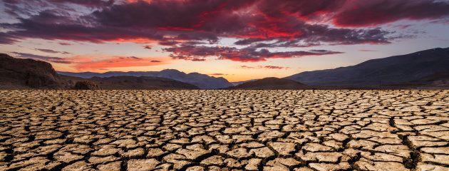 Sunset over cracked soil in the desert. Global warming