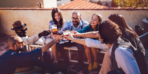 Multi-ethnic friends celebrating and toasting with wine and beer at rustic country house in Italy