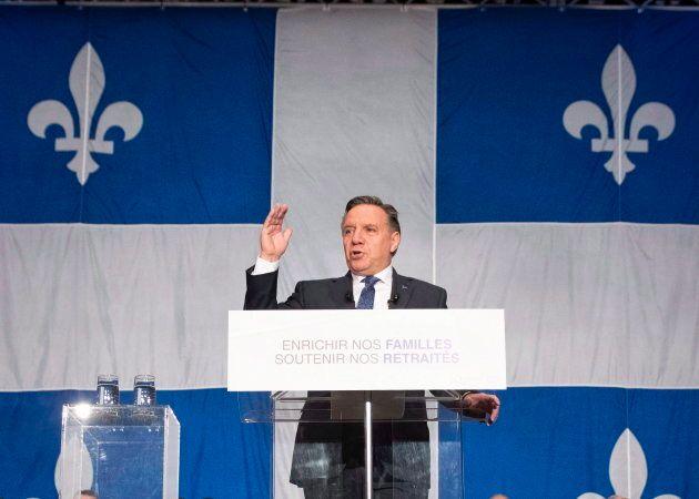 Le premier ministre du Québec devant un très grand drapeau lors de la mise à jour économique de la province,...