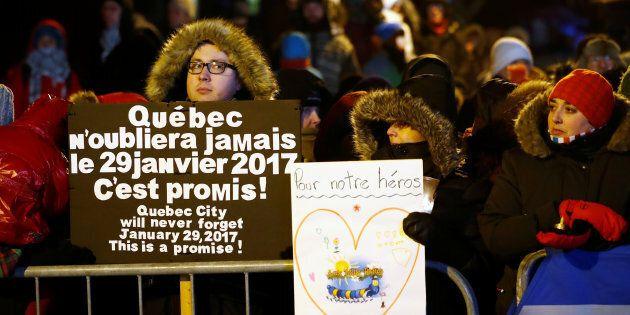 Les gens tiennent des pancartes de soutien lors d'une vigile soulignant la première Commémoration des...