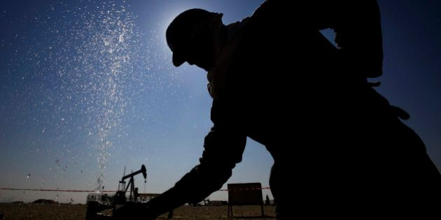An oil worker adjusts a valve releasing a spray of water while working on oil pipelines Thursday, Feb....