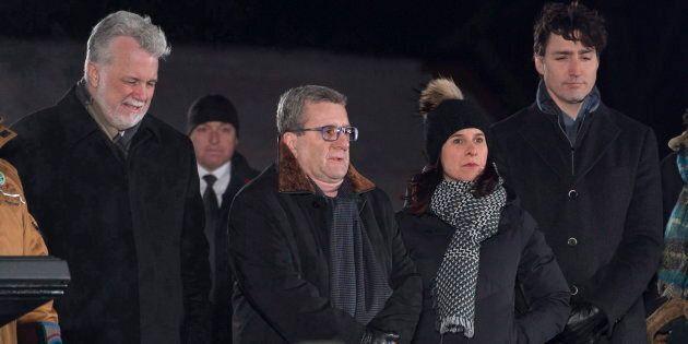 Le premier ministre du Québec (de l'époque), Philippe Couillard, à gauche, le maire de la ville de Québec, Régis Labeaume, la mairesse de Montréal, Valérie Plante, et le premier ministre, Justin Trudeau, assistent à une cérémonie organisée lors d'une veillée commémorant le premier anniversaire de la fusillade de la mosquée de Québec, le 29 janvier 2018.