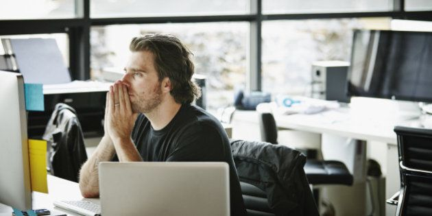 Businessman with hands on chin sitting at office workstation looking at computer monitor