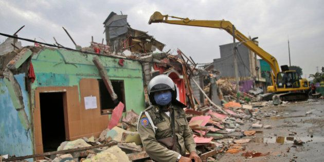 A city security officer stands guard as a backhoe demolishes buildings at Kalijodo shantytown which is...