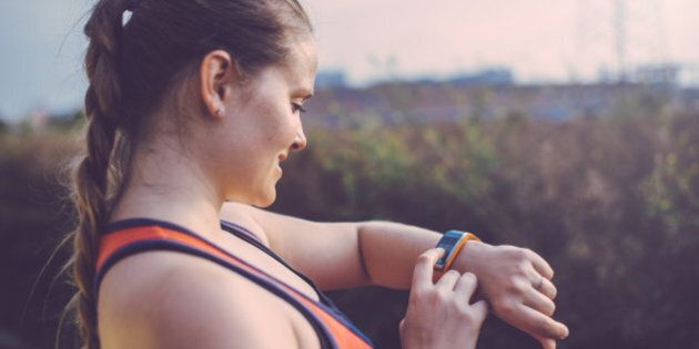Woman using smart watch outdoor before having a running