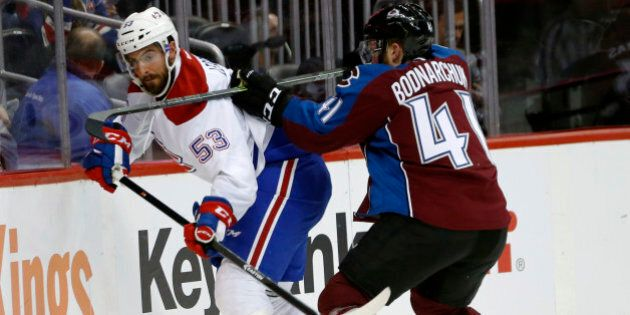 Montreal Canadiens left wing Lucas Lessio, left, is checked into the boards while passing the puck by...