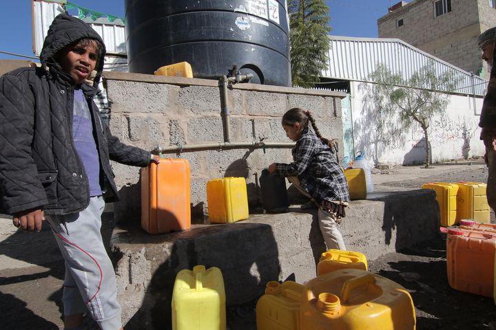 Le mercredi 13 décembre 2017 : Des enfants remplissent des jerricans d'eau potable à un réservoir d'eau situé dans une rue de Sanaa, dans le gouvernorat de Sanaa, au Yémen.