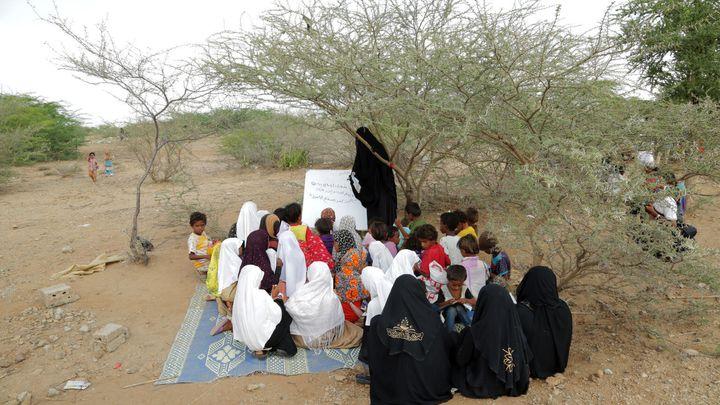 Le samedi 11 novembre 2017 : Les écoles étant détruites, le personnel enseignant au Yémen travaille avec ce qu'il a sous la main. Des élèves sont assis sous un arbre tandis qu'une enseignante donne un cours à Bait Al Faqueeh, dans le gouvernorat d'Al Hudaydah, au Yémen.