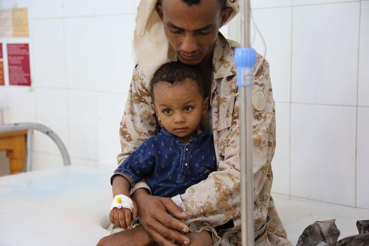 Le lundi 14 août 2017 : Un père tient son enfant souffrant du choléra alors que le petit reçoit un traitement à l'hôpital Alsadaqah d'Aden, au Yémen.