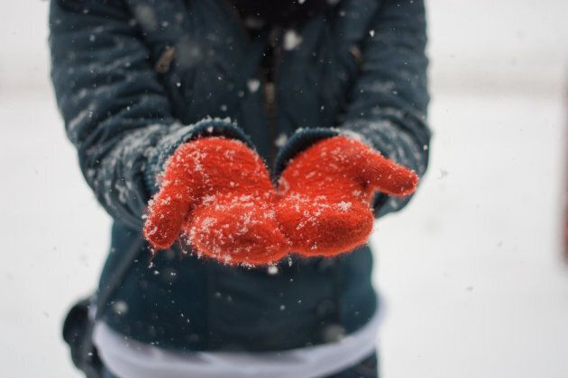 Girl catching snowflakes which are falling on her orange knitted gloves.