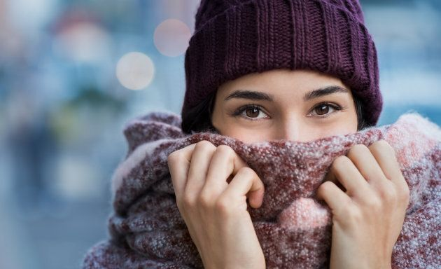 Winter portrait of young beautiful woman covering face with woolen scarf. Closeup of happy girl feeling...
