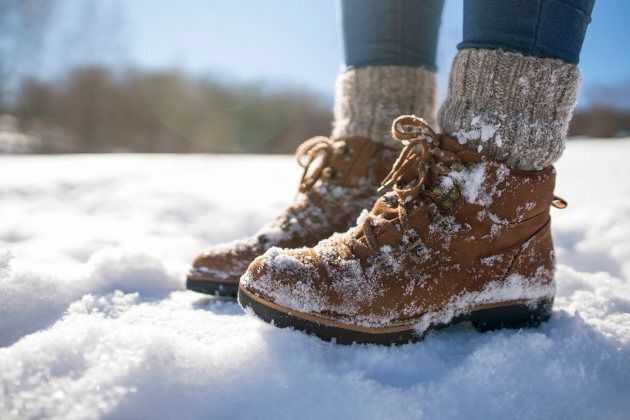 A pair of mountaineer's boots in the snow, close-up shot.