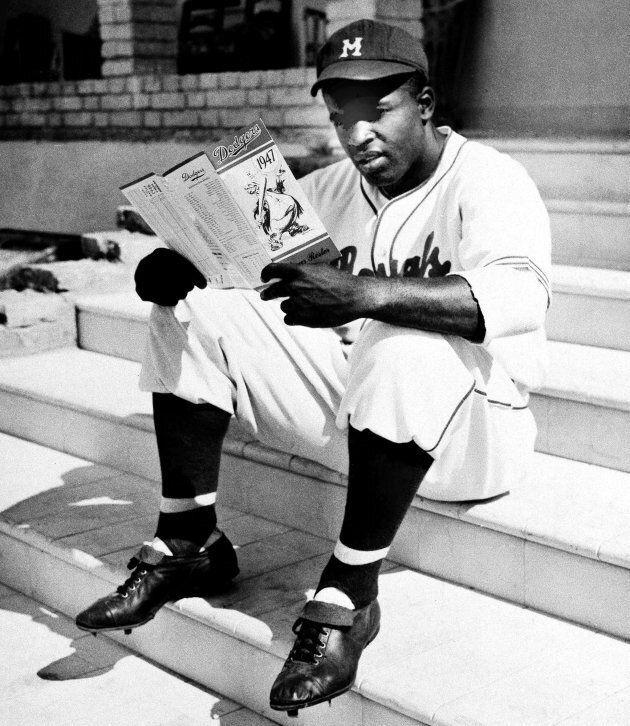 Dans cette photo du 27 février 1947, Jackie Robinson, des Royals de Montréal, examine une liste des Brooklyn Dodgers à La Havane, Cuba, où il s'entraîne avec son équipe.