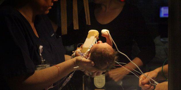 Un nouveau-né prématuré est pris en charge par une infirmière spécialisée de l'unité en néonatalogie de soins de longue durée.
