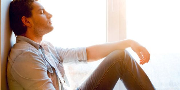 Side view of handsome young man sitting at the window sill and keeping eyes