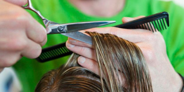 Male hairdresser cutting woman's hair short whilst holding comb,