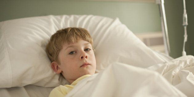 Young boy lying in hospital bed looking at camera with sad
