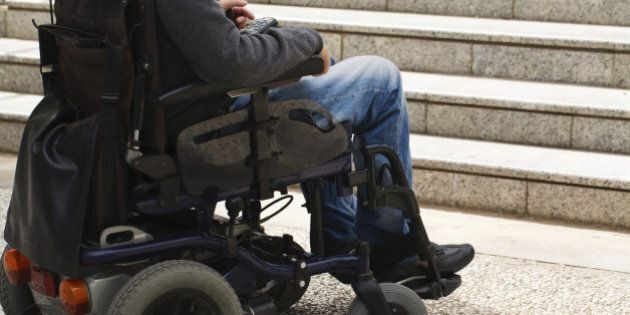Wheelchair user in front of staircase