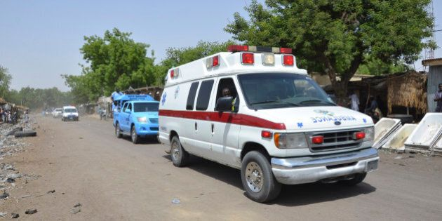 An ambulance and security cars drive to the site of a suicide bomb attack at a market in Maiduguri, Nigeria,...