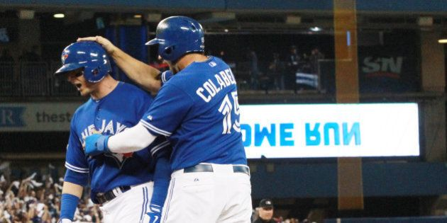 TORONTO, ON- OCTOBER 19:  Chris Colabello congratulates Troy Tulowitzki after he hit a home run. The Toronto Blue Jays and the Kansas City Royals play game three of the MLB American League Championship Series  at  Rogers Centre in Toronto.  October 19, 2015.        (Steve Russell/Toronto Star via Getty Images)