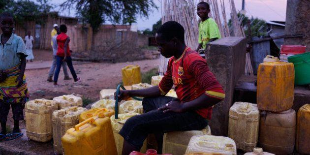 BUJUMBURA, BURUNDI - JUNE 27: A teenager fills water jugs at a neighborhood water pump on Monday on June...