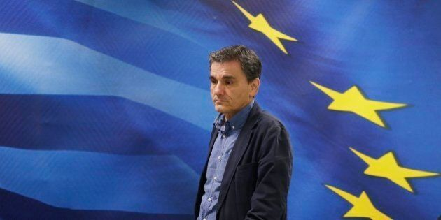 New Greek Finance Minister Euclid Tsakalotos arrives for a hand over ceremony in Athens, Monday, July...