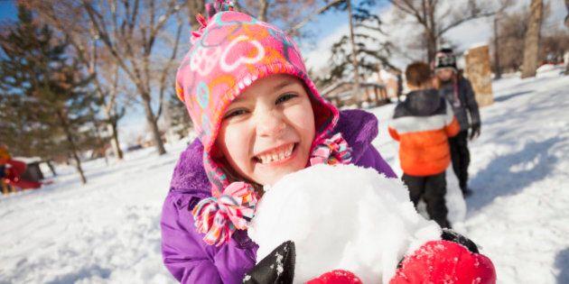 Caucasian girl holding snowball outdoors