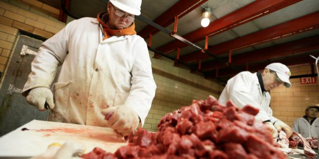 Amend Packing Company worker Chris Jorgensen, left, cuts stew meat, Tuesday, Feb. 17, 2015, in Des Moines, Iowa. Demand for local beef is surging but people who slaughter cattle and slice the beef into steaks say few people want to go into the business. Nationally, there were 1,200 federally inspected livestock slaughterhouses in the U.S. in 1990. By 2010 the number had dropped to 800. (AP Photo/Charlie Neibergall)