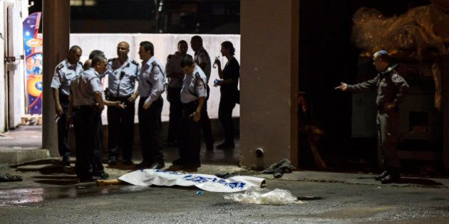 Israeli police stand by the shrouded body of Palestinian attacker in Beersheba, Israel, Sunday, Oct....