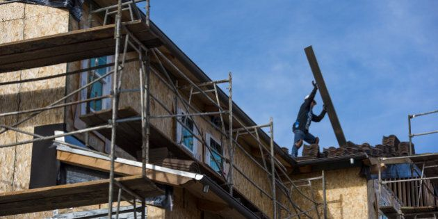 A contractor moves roofing material on a home under construction at the Toll Brothers Inc. Cantera at...