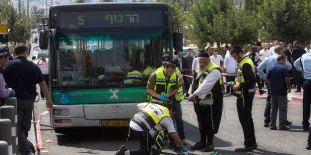 Israeli ZAKA emergency response members clean the scene of a stabbing attack in Jerusalem, Thursday,...