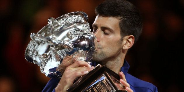 Novak Djokovic of Serbia kisses his trophy after defeating Andy Murray of Britain in the men's singles...