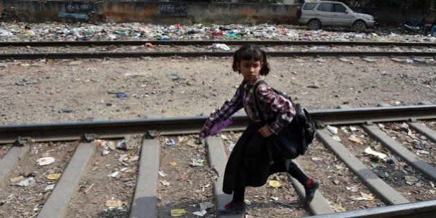 An Indian girl walks along train tracks in New Delhi on October 13, 2015 near where a four-year-old girl was raped. Indian police said they have arrested the main suspect in a horrific attack on a four-year-old girl who was raped and slashed with a blade before being abandoned by a railway track. AFP PHOTO / MONEY SHARMA (Photo credit should read MONEY SHARMA/AFP/Getty Images)