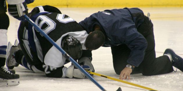 An injured hockey player is attended to on the ice by the team