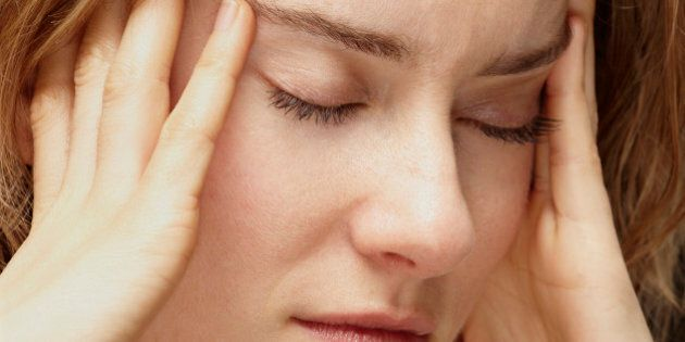 young woman with headache and holding her