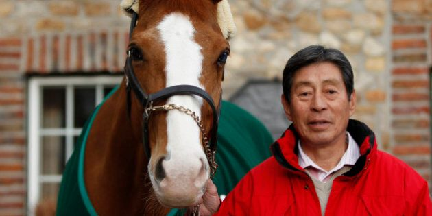 Japanese dressage rider Hiroshi Hoketsu poses with his horse Whisper at his stable in Aachen March 6,...