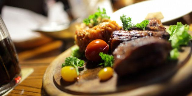 The pork ribs with vegetables on the wooden plate