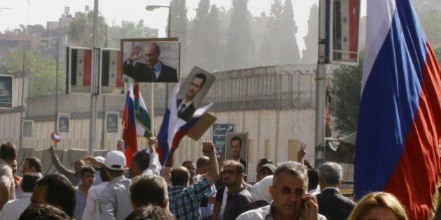 Several hundred people, holding up Russian and Syrian flags as well as portraits of the two countries' presidents, gather near the Russian embassy in Damascus on October 13, 2015 to express their support for Moscow's air war in Syria, just before two rockets struck the embassy compound sparking panic among the crowd.   AFP PHOTO/LOUAI BESHARA        (Photo credit should read LOUAI BESHARA/AFP/Getty Images)