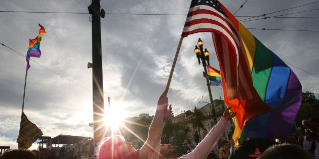 SAN FRANCISCO, CA - JUNE 27: A woman helps Francisco Pavon, center, wave a rainbow pride flag and an...
