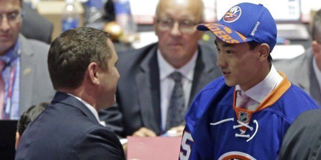 Andong Song, of China, shakes hands with a team executive after being chosen 172nd overall by the New...
