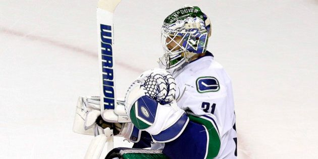 Vancouver Canucks goalie Eddie Lack celebrates after the third period of an NHL hockey game against the...