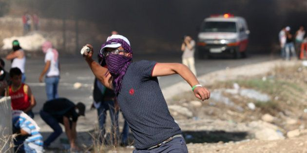 NABLUS, Oct. 11, 2015 -- A Palestinian protester hurls stones at Israeli soldiers during clashes at Hawara...