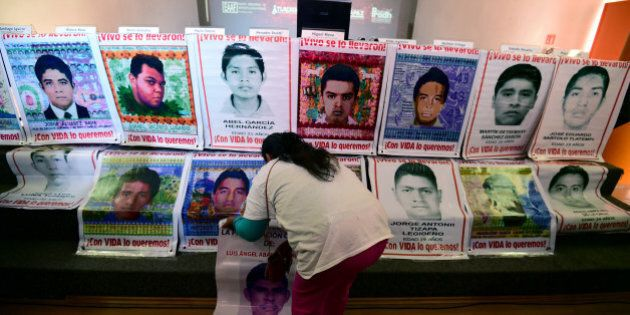 A relative of one the 43 missing students of Ayotzinapa sets up posters with their pictures before a...