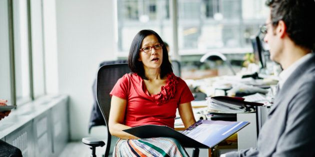 Businesswoman leading informal meeting with colleague at workstation in office